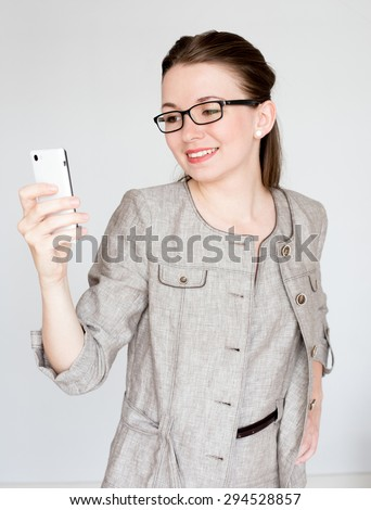Young business woman in office dress using her smart-phone - stock photo