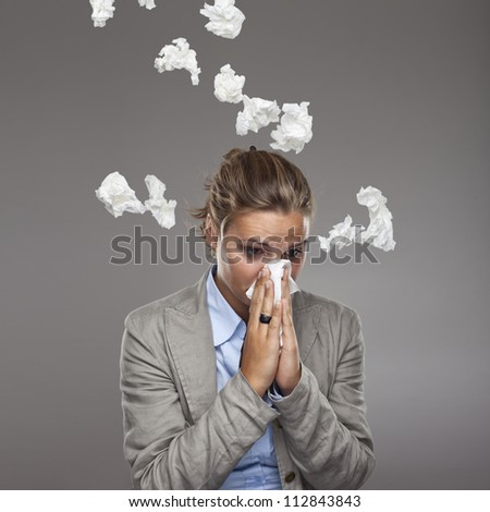 Young business woman in office under the rain of paper handkerchiefs - girl got a cold with lot of tissues - stock photo