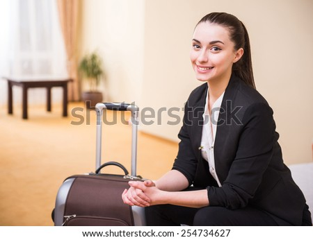 Young business woman is sitting at the hotel room with suitcase and looking at the camera. - stock photo