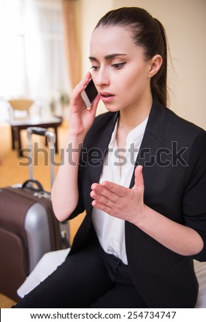 Young business woman is speaking by phone sitting in hotel room. - stock photo
