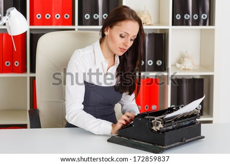 Young business woman is typing document with an old typewriter in the office. - stock photo