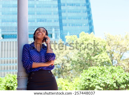 Young business woman laughing on cell phone outside office building - stock photo