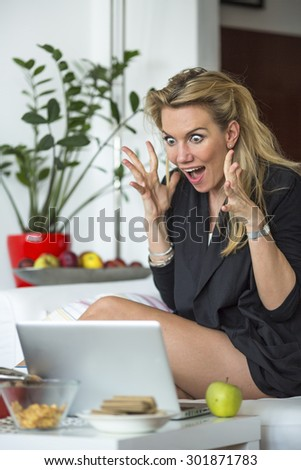 Young business woman looking at a laptop in a state of shock. Stress, fear, shock. - stock photo