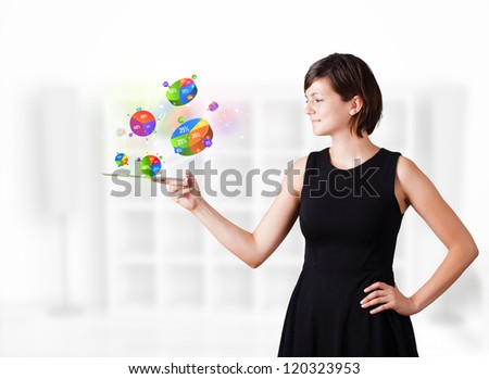 Young business woman looking at modern tablet with colourful pie charts - stock photo