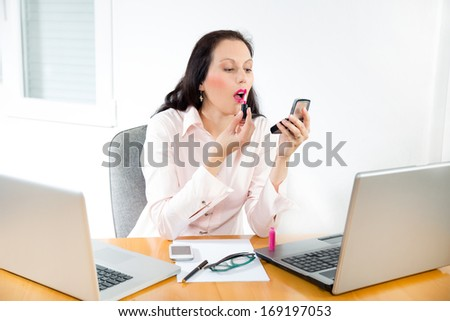 young business woman looking in the mirror and using lipstick in the office - stock photo
