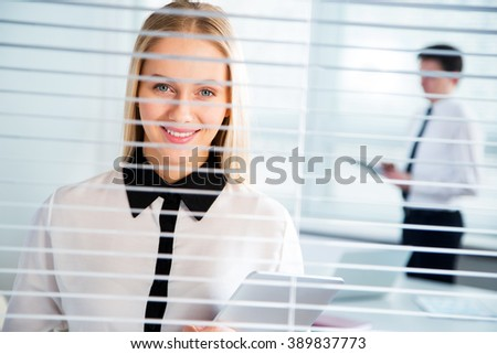 Young business woman looking through blinds - stock photo