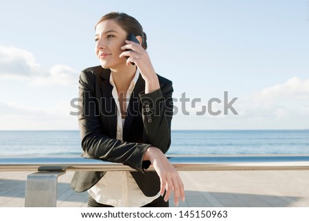 Young business woman making a phone call on her smartphone while leaning on a metallic banister near the sea during a sunny day with a blue sky, smiling and relaxed. - stock photo