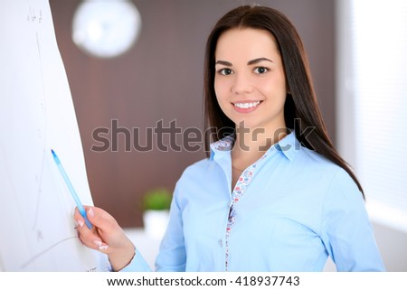 Young business woman pointing at flipchart in the office - stock photo