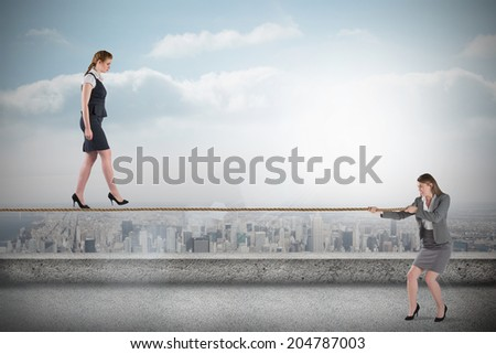 Young business woman pulling a tightrope for businesswoman against balcony overlooking city - stock photo