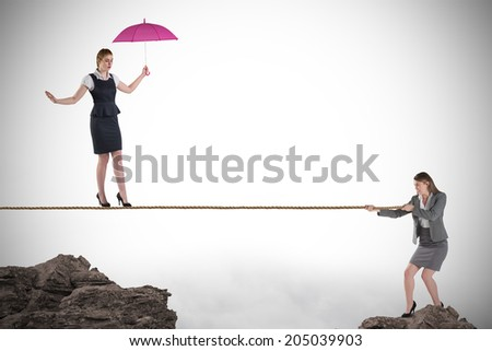 Young business woman pulling a tightrope for businesswoman against rocky landscape - stock photo