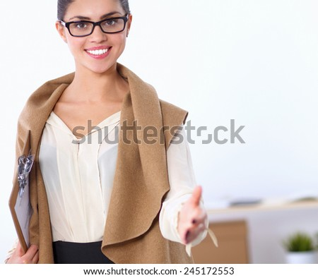 Young business woman ready to handshake standing in  office - stock photo