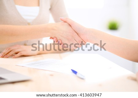 Young business woman shaking hands  after signing contract - stock photo