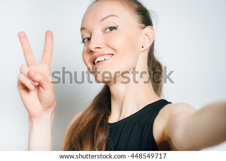 young business woman showing two fingers Victory sign isolated on a gray background - stock photo