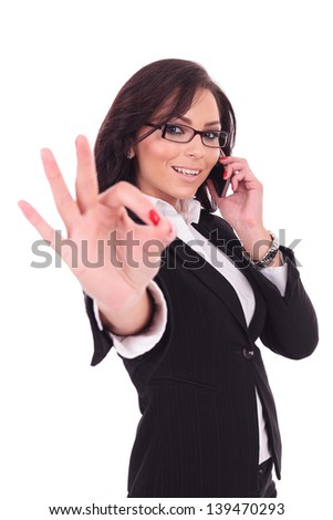 young business woman shows the ok sign while on the phone, smiling at the camera. on white background - stock photo