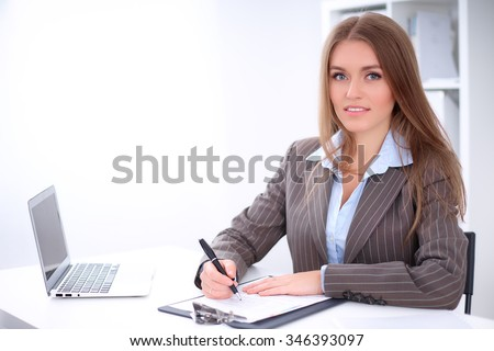 young business woman signing documents sitting at the desk on office background - stock photo