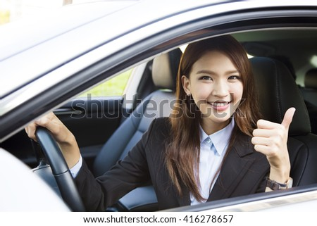 young business woman sitting in car and showing thumbs up - stock photo