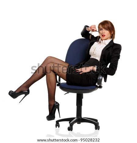 Young business woman sitting in office chair with cellphone on a white background - stock photo