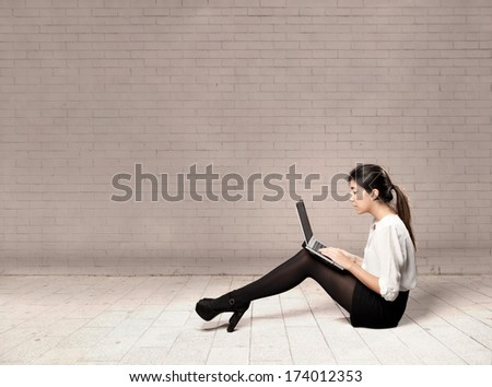 young business woman sitting on floor using a laptop - stock photo