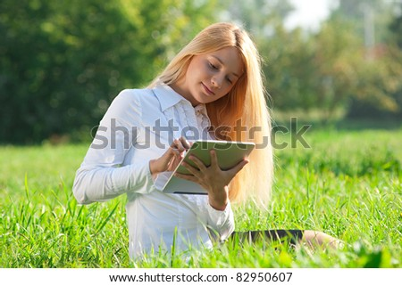 Young  business woman sitting on grass and using electronic tablet outdoors - stock photo