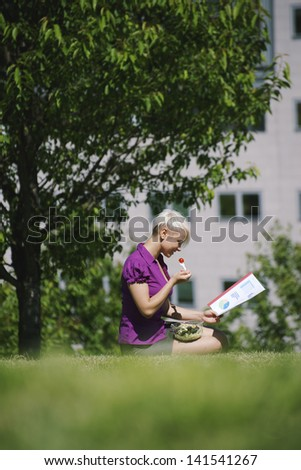 young business woman sitting on grass in park, eating salad for lunch and reading paperwork - stock photo