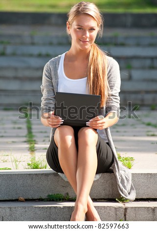 Young  business woman sitting on stairs and using laptop outdoors - stock photo