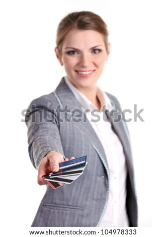 Young business woman smiling brightly and stretching out hand with plastic cards. Image with shallow depth of field, hand in focus. - stock photo