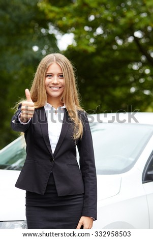 Young business woman standing in front of car and makes gesture with thumb up - stock photo