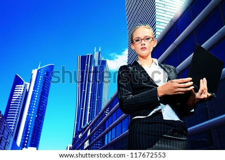 Young business woman standing with laptop in the big city. - stock photo