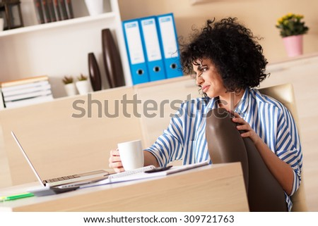 Young business woman taking coffee break in her office. Looking pensively. - stock photo