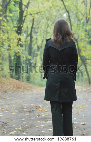 Young business woman taking relaxation walk in the park - stock photo