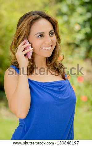 Young business woman talking phone in the park - stock photo