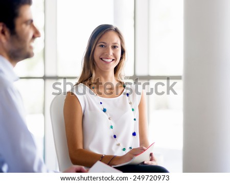 Young business woman talking to her collegue and smiling - stock photo