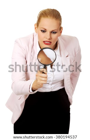 Young business woman using a magnifying glass - stock photo