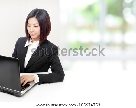 Young Business woman using computer and sit at company office with white table, window outside are green background, model is a asian beauty - stock photo