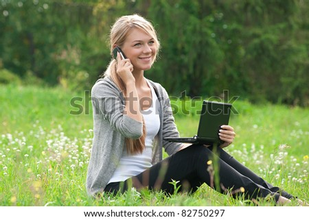 Young  business woman using laptop and talking on a cell phone outdoors - stock photo