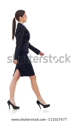 young business woman walking. She is smiling and looking away from the camera isolated over white background - stock photo