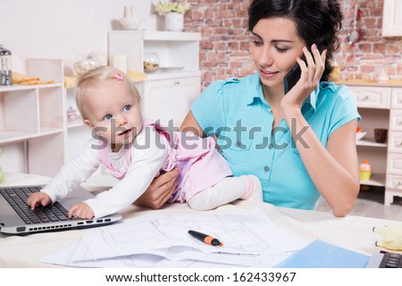 Young business woman with baby in the kitchen working with laptop, speaks by phone - stock photo