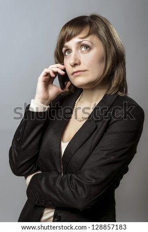 Young business woman with brunette hair and black clothes is using a mobile cell phone - stock photo