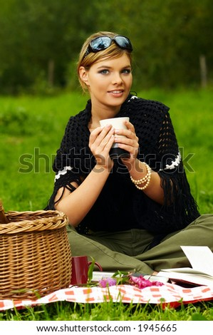 Young business woman with cup during picnic on green meadows outdoors - stock photo