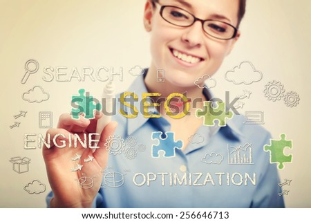Young business woman with eyeglasses drawing SEO concepts - stock photo