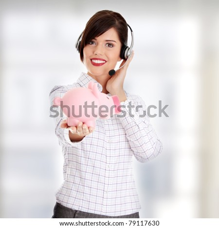 Young business woman with headset holding piggy bank - stock photo