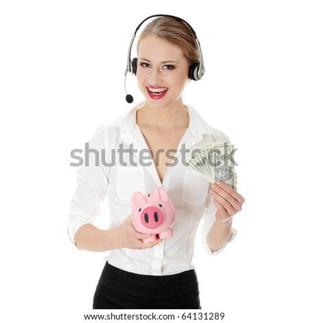 Young business woman with headset holding piggy bank and money - stock photo