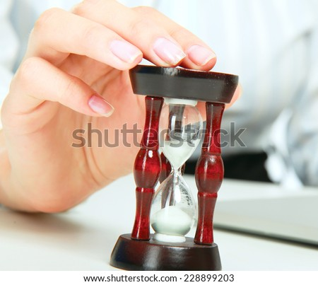 Young business woman with hourglass - time concept. - stock photo