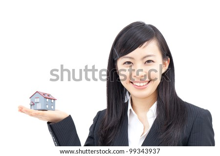 Young business woman with house model, isolated on white background - stock photo