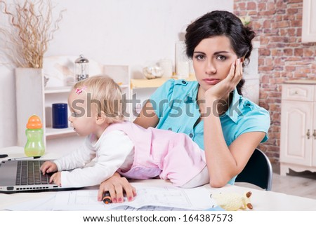 Young business woman with laptop and her baby girl - stock photo