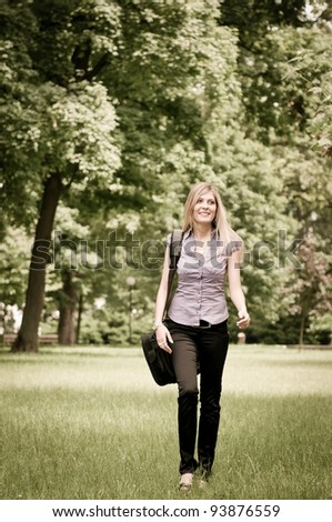 Young business woman with laptop bag walking outdoors in park - stock photo