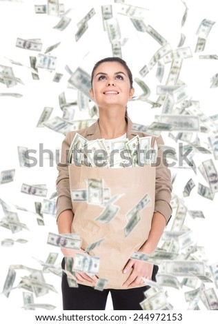 Young business woman with paper bags full of money and money banknotes flying in air on the white background. - stock photo