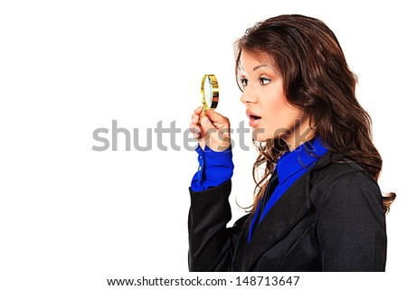 Young business woman with surprise looks through a magnifying glass. Isolated over white. - stock photo