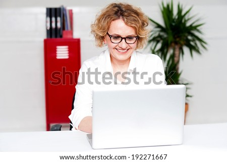 Young business woman working on her laptop - stock photo