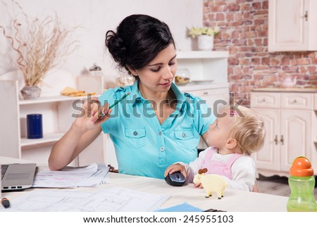 Young business woman working with baby in the kitchen  - stock photo